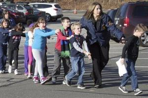 In this photo provided by the Newtown Bee, Connecticut State Police lead children from the Sandy Hook Elementary School in Newtown, Conn., Friday.