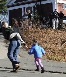 A mother runs with her children as police above canvass homes in the area following a shooting at the Sandy Hook Elementary School in Newtown.