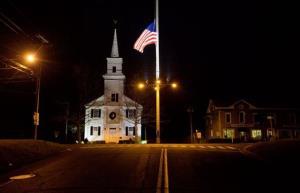 A U.S. flag flies at half-staff on Main Street in Newtown, Conn.