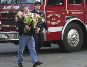 Volunteer firefighters carry flowers to a makeshift memorial near the Sandy Hook Elementary School Saturday.