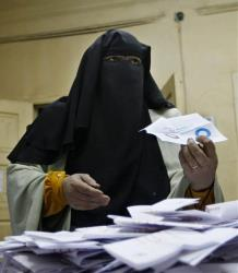 An Egyptian referendum official counts votes at a polling station in Cairo, Egypt, late Saturday, Dec. 15, 2012.