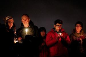 People hold candles in silence during a vigil in remembrance of the Newton, Conn. shooting victims at Green Lake Park in Seattle on Saturday, December 15, 2012.