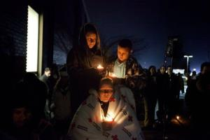 A family listens to a memorial service outside Newtown High School for the victims of the Sandy Hook Elementary School shooting, Sunday, Dec. 16, 2012, in Newtown, Conn.
