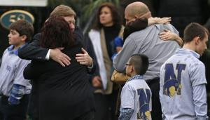 Families embrace while surrounded by children wearing Newtown school shirts outside the funeral for six-year-old shooting victim Jack Pinto in Newtown, Conn., Monday, Dec. 17, 2012.