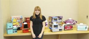 In this photo provided by Hasbro, McKenna Pope poses in front of earlier models of the Easy-Bake Oven during her trip to the Hasbro headquarters in Pawtucket, RI, Dec. 17, 2012.