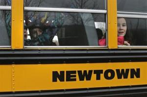 Schoolchildren look out the window of their bus as they head back to school in Newtown, Conn., Tuesday. Classes did not resume at Sandy Hook Elementary.