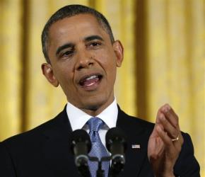 Barack Obama gesturing while answering a question during a news conference in the East Room of the White House in Washington.