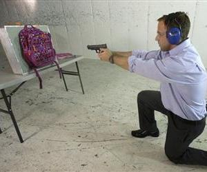Rick Brand, COO of Amendment II, shoots a 9 mm pistol into a children's backpack, left, fitted with an anti-ballistic insert during a demonstration at a gun range, Dec. 19, 2012, in Taylorsville, Utah