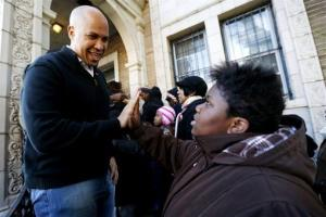 In this Nov. 9, 2012, photo, Cory Booker greets 13-year-old Blonbzell Taylor outside of a resource center where residents impacted by Superstorm Sandy received clothing donations in Newark, NJ.