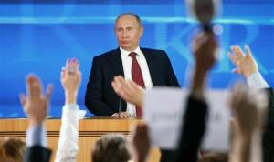 Members of the media raise their hands to ask questions of Russian President Vladimir Putin.