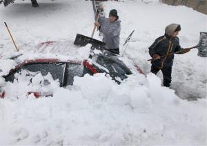 Luke McHenry, left, and his son, Sebastian Wells, dig out their snow-buried vehicle as residents in Madison, Wis. contend with a severe winter storm Thursday, December 20, 2012.
