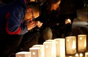 A man reacts placing candles on a makeshift memorial in honor of the victims who died a day earlier when a gunman opened fire in an elementary school, Saturday, Dec. 15, 2012, in Newtown, Conn.