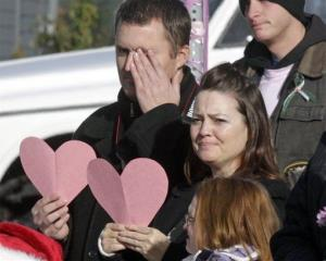 Mourners line the street as a hearse carrying Emilie Parker drives by following funeral services for the 6-year old Connecticut elementary shooting victim, Saturday, Dec. 22, 2012, in Ogden, Utah.