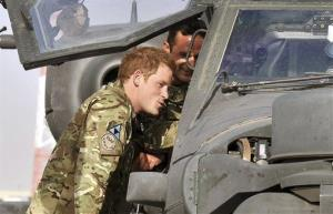This July 9, 2012, photo shows Prince Harry examining the cockpit of an Apache helicopter with a member of his squadron at Camp Bastion in Afghanistan.