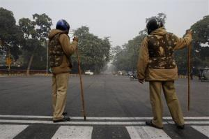 Indian policemen block a road to prevent protests in central New Delhi, India, Monday, Dec. 24, 2012.