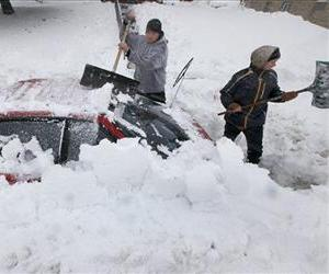 Luke McHenry his son dig out their snow-buried vehicle as residents in Madison, Wis. contend with a severe winter storm that moved through the upper Midwest, December 20, 2012.