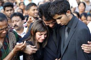 Benedict Barboza holds his son Junal and daughter Lisha during the burial of their mom, Jacintha Saldanha, at her hometown Shirva, India, Monday, Dec. 17, 2012.