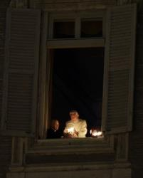 Pope Benedict XVI lights a candle at his studio window overlooking St. Peter's Square at the Vatican, after the unveiling of the Nativity scene, Monday, Dec. 24, 2012.