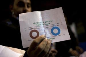 In this Saturday, Dec. 22, 2012 file photo, an Egyptian election worker shows an invalid ballot while counting ballots at the end of the second round of a referendum on a disputed constitution.