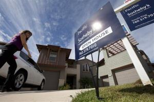 In this Nov. 14, 2012, photo, a woman walks towards a home for sale during a viewing for brokers in Leucadia, Calif.