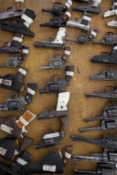 Weapons handed over by their owners lay on a table during a government program that accepts gun owner's weapons in exchange for bicycles, computers, tablets or money, on Christmas Eve in the Iztapalapa neighborhood of Mexico City, Monday, Dec. 24, 2012. Mexico City is sponsoring the program after 10-year-old Hendrik...