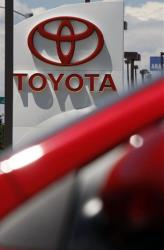 In this July 27, 2008 file photo, the company sign hangs over a row of 2009 models at a Toyota dealership in the southeast Denver suburb of Centennial, Colo.