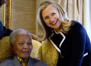 FILE - In this Aug. 6, 2012 file photo, U.S. Secretary of State Hillary Rodham Clinton, right, meets with former South Africa President Nelson Mandela, 94, at his home in Qunu, South Africa. There may be no living figure so revered as Mandela around the world as a symbol...