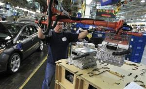 Assemblyman Mark Lynett lifts an inverter system converter for a hybrid vehicle on the assembly line at the Ford Michigan Assembly Plant in Wayne, Mich., Nov. 8, 2012.