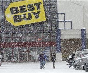 People walk in the parking lot of a Best Buy store during a severe snow storm in North Olmsted, Ohio Wednesday, Dec. 26, 2012.
