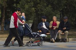 In this April 28, 2011 file photo, elderly men rest on a bench as a family with their new born baby walk past at a park in Beijing, China.