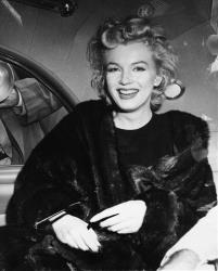 Marilyn Monroe smiling in a car after arriving tousled from an all-night plane flight from Hollywood to Idlewild Airport, in New York.