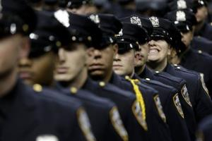 A new police officer grins during a police academy graduation ceremony in New York, Friday, Dec. 28, 2012.