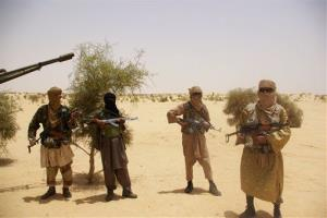 In this April 24, 2012 file photo, fighters from Islamist group Ansar Dine stand guard during a hostage handover in the desert outside Timbuktu, Mali.