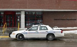 A Detroit Police officer guards the entrance to the department's 6th Precinct in Detroit, Monday, Jan. 24, 2011, after a shooting there.