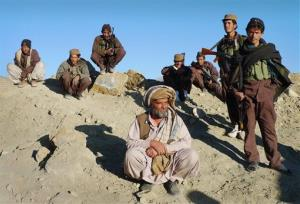 In this Thursday, Dec. 1, 2011 photo, members of the Afghan Local Police watch passing US troops visiting their base in Sar Hawza district of Paktika province, south of Kabul, Afghanistan.