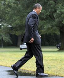 President Barack Obama sidesteps a puddle as crosses the White House South Lawn.