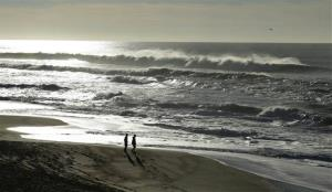 A couple walk along the North Beach as a helicopter searches for a man lost in the high surf Tuesday at the Point Reyes National Seashore, Calif.