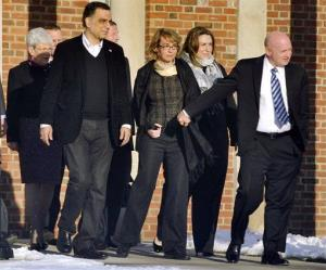 Gabrielle Giffords, center, holds hands with her husband, Mark Kelly, while exiting Town Hall at Fairfield Hills Campus in Newtown, Conn., on Friday.