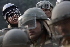 An Indian police officer, left, sports a cricket helmet as policemen stand near barricades in New Delhi, India, on Dec. 27.