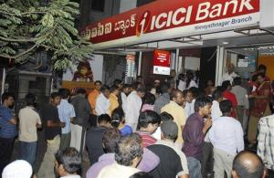 ICICI customers stand in a queue to withdraw money outside an ICICI ATM after rumors of the bank being in financial crises, in Hyderabad, India, late Monday, Sept. 29, 2008.