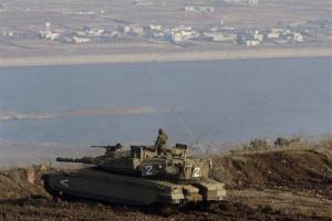 An Israeli soldier stands on top of a tank overlooking the Syrian village of Bariqa, near the Israel-Syria border in the Golan Heights.