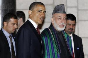 In this May 2, 2012, photo, President Barack Obama and Afghan President Hamid Karzai walk together after they signed a strategic partnership agreement at the presidential palace in Kabul, Afghanistan.