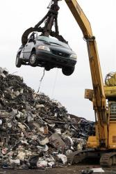In this Aug. 6, 2009 photo, a crane lifts a flattened car to a shredder at Gershow Recycling Corp. in Medford, NY.