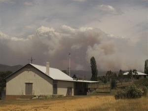 Wildfire smoke rises from hills behind the village of Numeralla in New South Wales, Jan. 8, 2013.