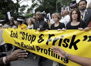 In this June file photo, the Rev. Al Sharpton, center, walks with demonstrators during a silent march to end the stop-and-frisk program in New York.