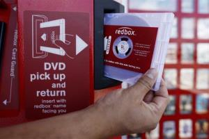 A rental DVD is dispensed from a Redbox kiosk.