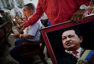 A Venezuelan embassy worker holds a framed image of Venezuela's ailing President Hugo Chavez.
