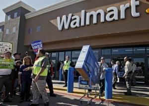 Shopper Jose Alvarez, right, carries out a newly-purchased television past protestors outside a Walmart store Friday Nov. 23, 2012, in Paramount, Calif.
