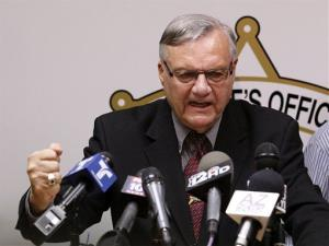 In this May 10, 2012 file photo, a defiant Maricopa County Sheriff Joe Arpaio pounds his fist on the podium as he answers questions during a news conference in Phoenix.