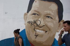 Pedestrians walk past a mural of Venezuela's President Hugo Chavez in Caracas, Venezuela, Wednesday.